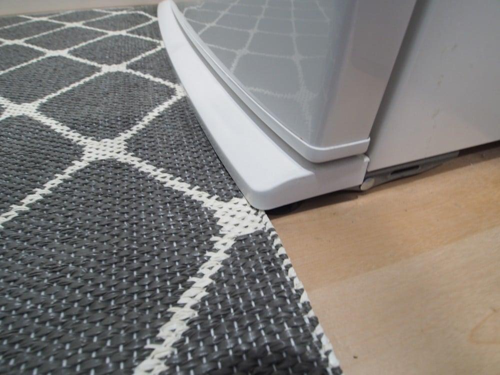 冷蔵庫の下にキッチンマットを滑り込ませる