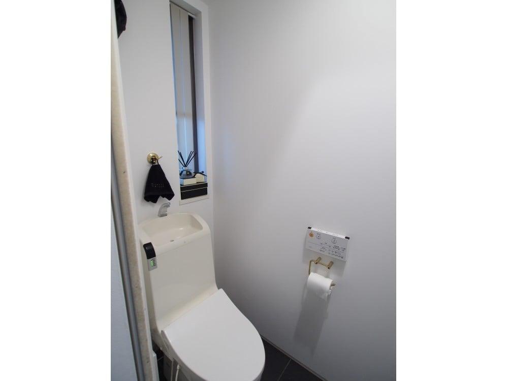 モノトーン+ゴールドでまとめられたトイレ