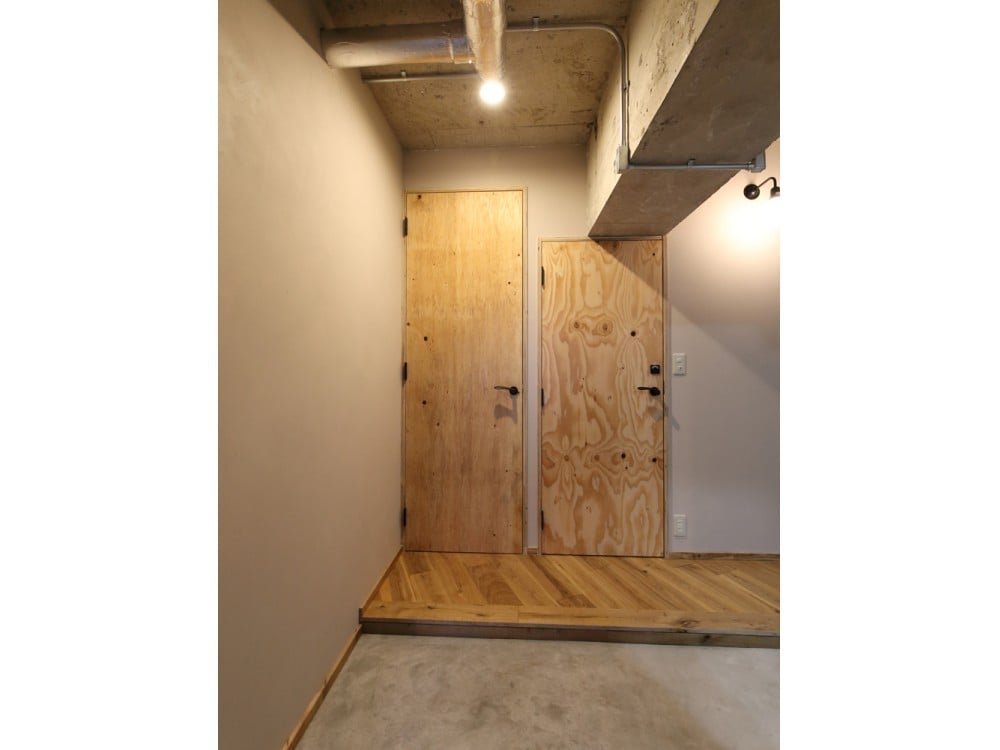コンクリート打ち放しの天井とモルタルの土間が特徴の玄関