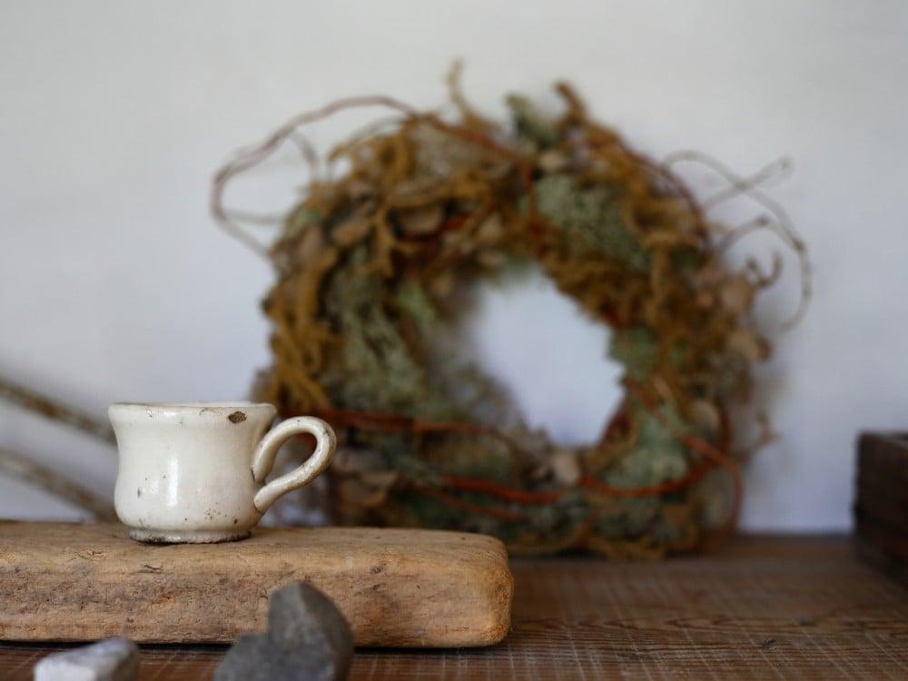 飾り棚に飾られた小さなアンティークのカップ