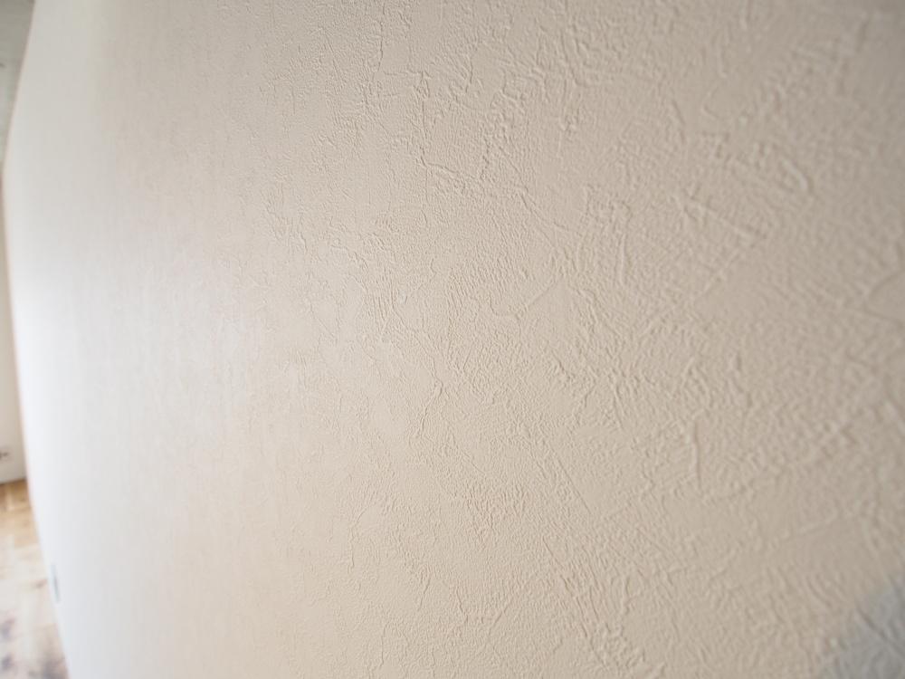 素材感のある壁と天井に合わせたシンプルなクロス