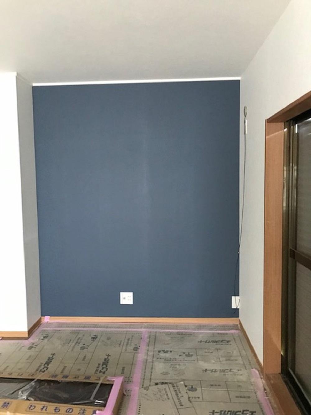 テレビボードを置く壁にネイビー系のアクセントクロスを。